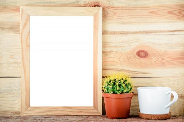 Moldura de madeira vazia com cacto e copo branco sobre fundo de madeira