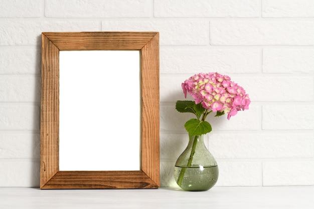 Moldura de madeira vazia e flor em vaso de vidro