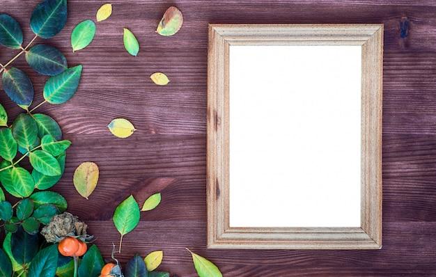 Moldura de madeira vazia na superfície de madeira marrom entre folhas verdes e amarelas