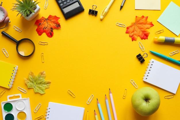 Moldura de material escolar cadernos lápis e canetas clipes de papel tintas lupa maçã