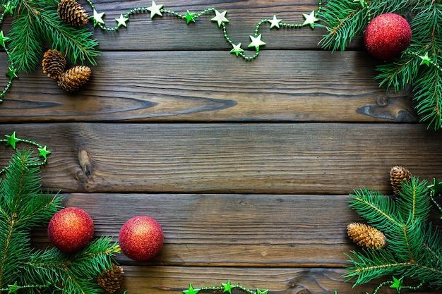 Moldura de natal com cones de ramos de pinheiro em vista de mesa de madeira escura com espaço para texto