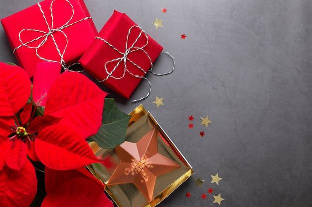 Moldura de natal com flores de poinsétia vermelha presentes embrulhados, decoração dourada e confetes em cinza