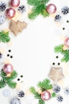 Moldura de natal com galhos de árvores de abeto luzes de natal decorações em rosa e bege