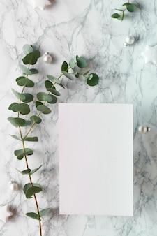 Moldura de natal com galhos de eucalipto frescos e bugigangas brancas com estrelas negras. plano de fundo de mármore leigos, página de papel em branco, com cópia-espaço, espaço para texto ...