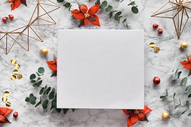Moldura de natal com galhos de eucalipto frescos, flores de poinsétia vermelha, decorações geométricas - hexágonos, formas de arame. na moda plana leiga, vista superior em fundo de mármore. cópia-espaço em tela branca.