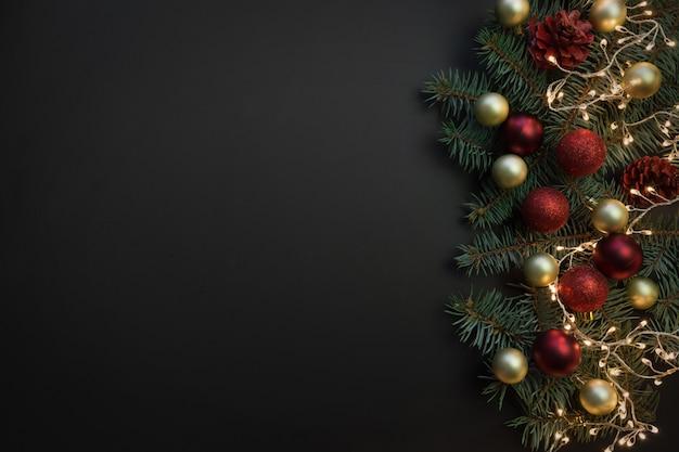Moldura de natal com galhos de pinheiro, bolas vermelhas e douradas, guirlanda de natal em fundo preto.