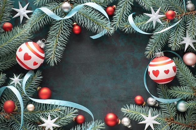 Moldura de natal com galhos de pinheiro, bugigangas em vermelho e prata, estrelas e fitas