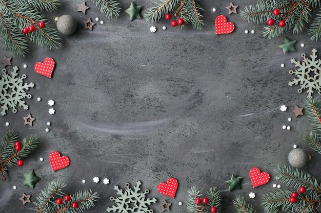 Moldura de natal com galhos de pinheiro, bugigangas em vermelho e verde, estrelas, corações, bagas e flocos de neve,