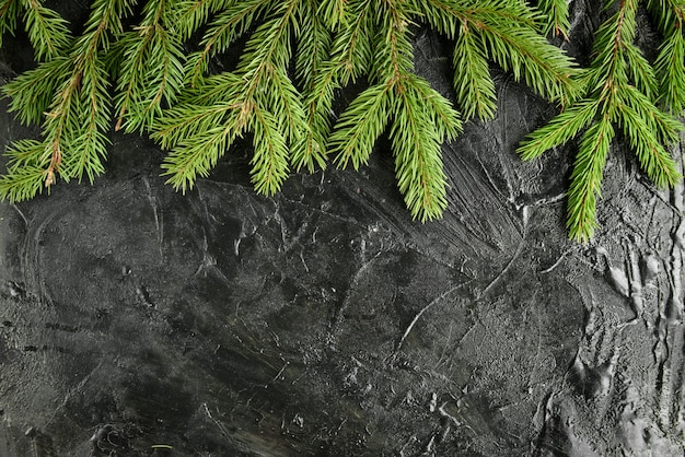 Moldura de natal com galhos de pinheiro, caixa de presente e pinhas na superfície preta.