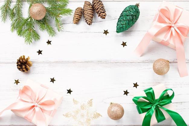 Moldura de natal com galhos de pinheiro, presentes embrulhados nas cores rosa e verdes, confetes. plano de natal, cópia espaço, vista superior