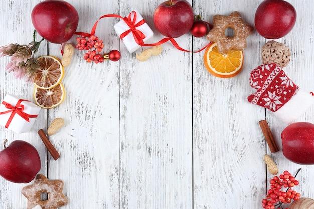 Moldura de natal com maçãs, biscoitos e enfeites