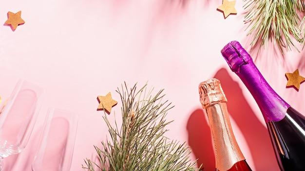 Moldura de natal com pinheiro, sombras, garrafas de champanhe, copos rosa