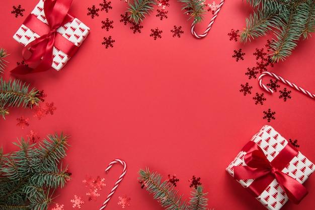 Moldura de natal com presentes, bolas, abeto, sobre fundo vermelho. cartão de felicitações feliz ano novo.