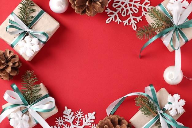 Moldura de natal com presentes, bolas, flocos de neve em fundo vermelho. cartão de felicitações.