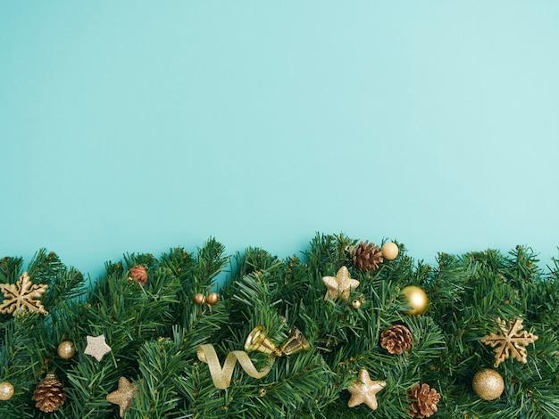 Moldura de natal com ramos de pinheiro e decorações em fundo azul claro