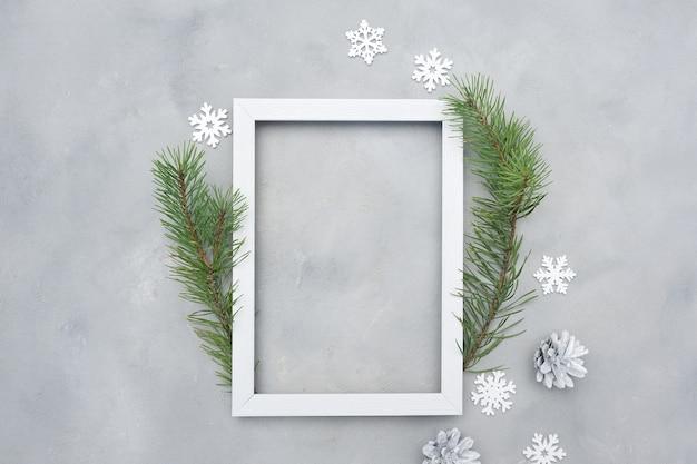 Moldura de natal de foto branca com lugar para texto. simulação de férias. flocos de neve e cones no fundo cinza.