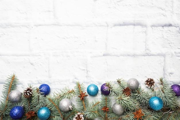 Moldura de natal feita de abeto, enfeites de árvore de natal em prata e azul sobre um fundo de tijolo claro. copie o espaço. postura plana.