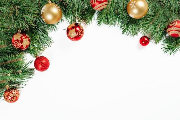 Moldura de natal, galhos de árvores com ouro e bolas vermelhas isoladas no branco. isolar.