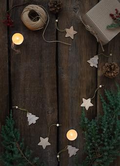Moldura de natal verde de galhos de árvores frescas, brinquedos de madeira de natal e luzes