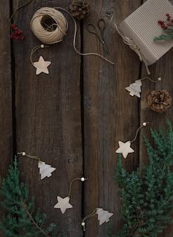 Moldura de natal vintage com galhos de árvores frescas, cones, brinquedos de natal de madeira