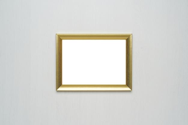 Moldura de ouro na parede de madeira branca