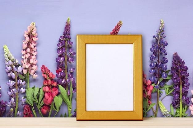 Moldura de ouro vazia para foto no pano de fundo das flores.