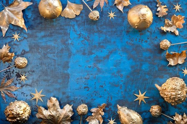 Moldura de outono no clássico azul e folhas douradas metálicas, abóboras, frutas e estrelas