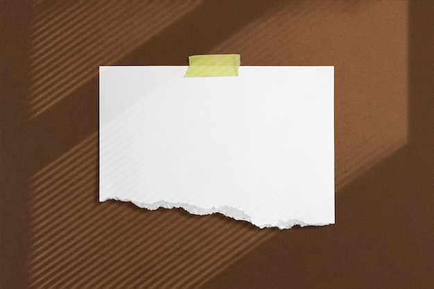 Moldura de papel rasgado em branco colada com fita adesiva na parede texturizada marrom com sombras suaves nas janelas