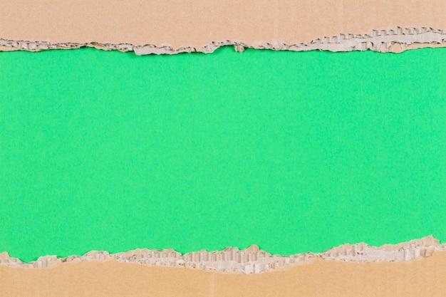 Moldura de papelão ondulado marrom com borda irregular na parede amarela