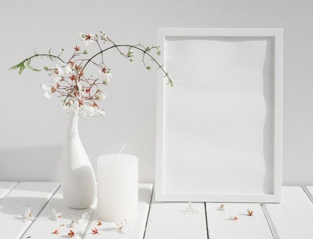 Moldura de pôster de convite branco, vela e lindas flores de clerodendron em um vaso de cerâmica na mesa de madeira no interior do quarto branco