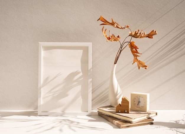 Moldura de pôster de madeira branca simulada, folha seca de filodendro em vaso, livros de relógio, modelo de casa em mesa bege