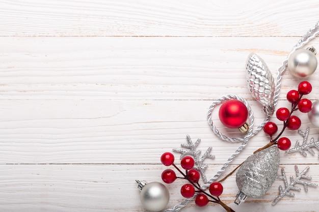 Moldura de prata decoração de natal vermelho sobre fundo branco de madeira