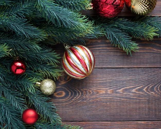 Moldura de ramos de abeto vermelho e dourado, bolas de árvore de natal em um fundo de madeira marrom