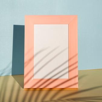 Moldura de retrato rosa em um fundo azul com uma sombra de palmeira