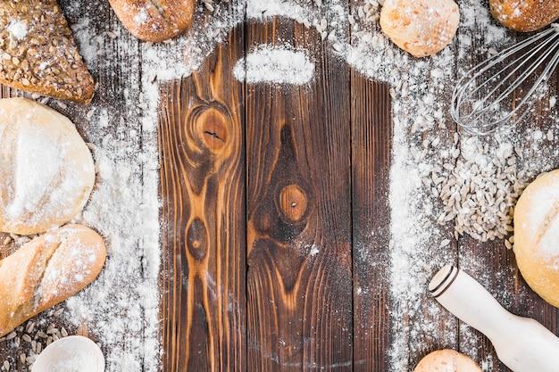 Moldura de tábua de cortar com farinha espalhada e pães de pão rodeados