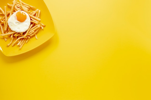 Moldura de vista superior com ovo e batatas fritas no prato