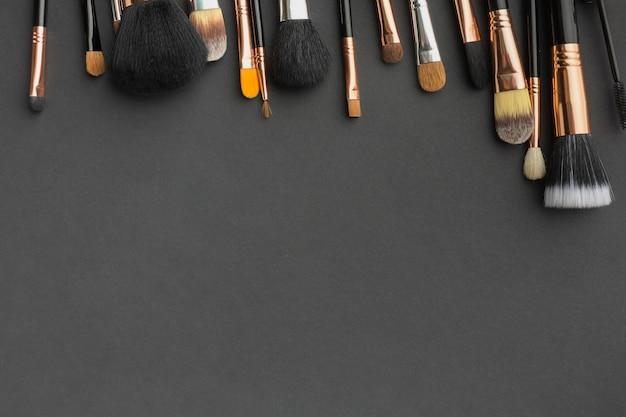 Moldura de vista superior com pincéis de maquiagem e fundo preto