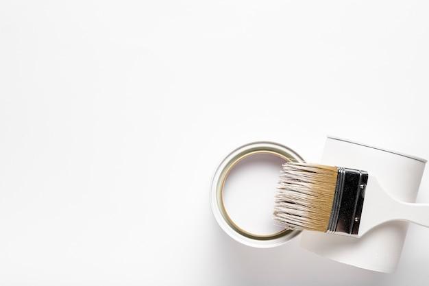 Moldura de vista superior com recipiente de tinta e pincel