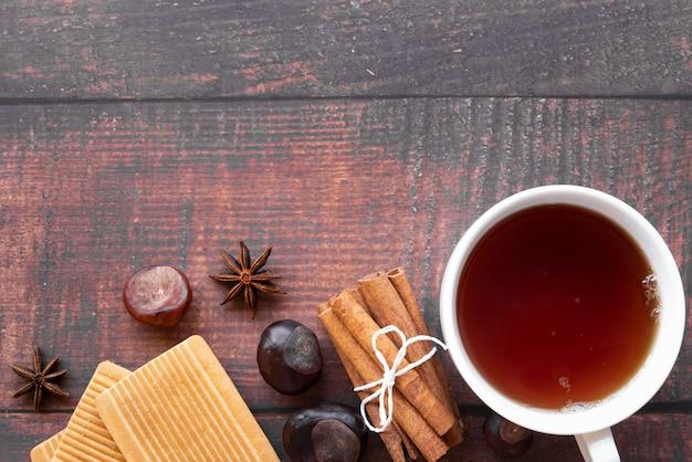 Moldura de vista superior com xícara de chá e fundo de madeira