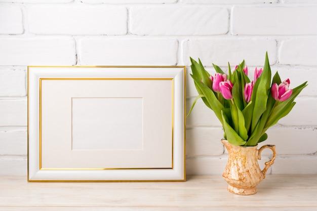 Moldura decorada ouro com tulipas cor de rosa brilhantes em vaso dourado