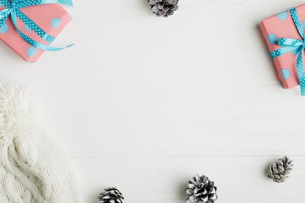 Moldura decorativa, atributos de natal em uma mesa de madeira branca.