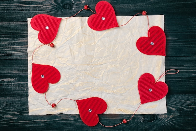 Moldura decorativa de corações vermelhos em papel amassado velho.