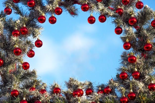 Moldura decorativa de uma árvore de natal decorada em um fundo de céu azul