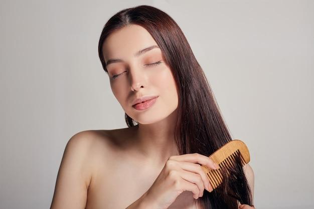 Moldura do meio, uma mulher com humor brincalhão penteia o cabelo com um pente marrom claro com os olhos fechados