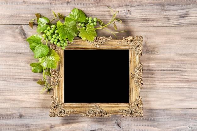 Moldura dourada com uvas e decoração de folhas de videira verdes na mesa de madeira