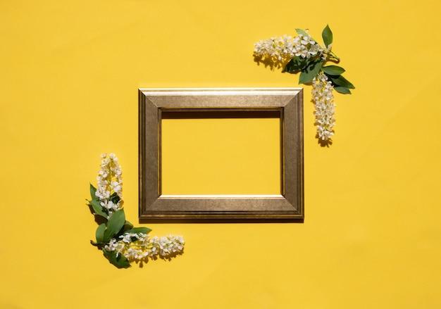 Moldura dourada de flores brancas e folhas em um fundo amarelo
