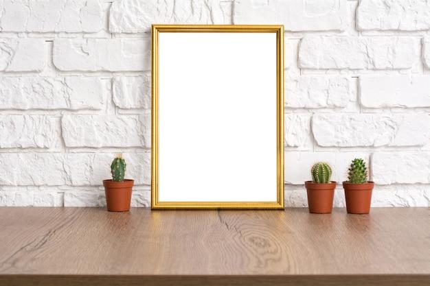 Moldura dourada em branco de maquete com lugar para texto ou imagem e cacto na mesa de madeira