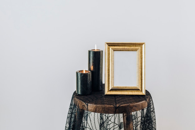 Moldura dourada em uma toalha de mesa de renda de aranha com velas pretas acesas