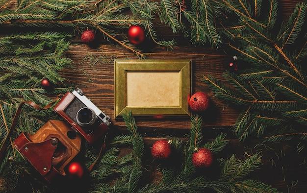 Moldura e câmera vintage em uma mesa ao lado da decoração de natal