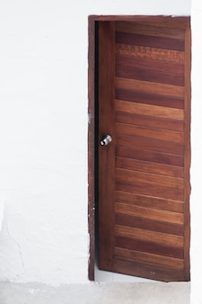 Moldura e painel da porta de madeira no fundo da parede branca, imagem frontal de uma porta de madeira aberta